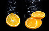 Slice of orange in the water with bubbles — Stock Photo