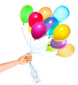 Wooden hand gives flying balloons — Stock Photo