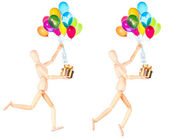 Wooden Dummy holding gift and flying balloons — Stock Photo
