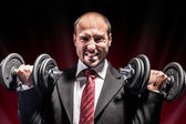 Businessman lifting weights — Stock Photo