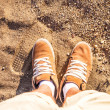 Stock Photo: Pair of Boots Shoes man's Foot on sand