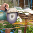 Angle Grinder Metal sawing with flashing sparks close up and Repairman hands home repair garden working summer time. Also called Circular Saw handheld electric instrument — Stock Photo