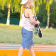 Boy Child going with Skateboard behind view Outdoor Summer Sport with nature on background — Photo #27500833