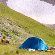 Stock Photo: Camping Tent in Mountains with MHiker sitting on grass and Glacier Hillside on Background