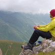 Stock Photo: MHiker in Mountains relaxing sitting on rocky cliff with clouds on background