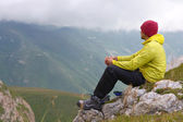 Man Hiker in Mountains relaxing sitting on rocky cliff with clouds on background — Stock Photo