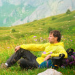 Stock Photo: Young MTraveller with backpack sitting on grass with flowers relaxing with Mountains on Background