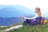 Woman Traveller with backpack sitting on grass with flowers relaxing with Mountains on Background — Stock Photo