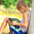 Stock Photo: Boy Child playing with Tablet PC sitting on skateboard Outdoor with forest on background Game Dependence concept