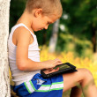 Stock Photo: Boy Child playing with Tablet PC Outdoor with forest on background Computer Game Dependence concept
