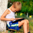 Boy Child playing with Tablet PC Outdoor with forest on background Computer Game Dependence concept — Stock Photo