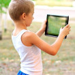 Stock Photo: Boy Child playing with Tablet PC standing Outdoor with nature on background Computer Game Dependence concept