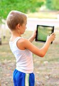 Boy Child playing with Tablet PC standing Outdoor with nature on background Computer Game Dependence concept — Stock Photo