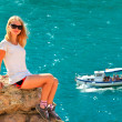 Stock Photo: Young Womrelaxing on rocky cliff with blue Seand Ship yacht on background Summer Traveling and Healthy Lifestyle concept