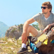 Young Man Traveler with backpack relaxing on Mountain summit roc — Stock Photo