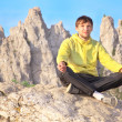 Man Traveler Relaxing Yoga Meditation sitting on stones with Rocky Mountains peak Ai-Petri and blue sky on Background — Stock Photo