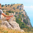 Man Traveler Relaxing Yoga Meditation sitting on stones with Rocky Mountains and blue sky on Background Harmony with nature concept — Stock Photo