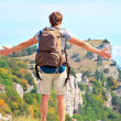 Stock Photo: MTraveler with backpack standing outdoor hands raised to blue sky with mountains on background Freedom and Healthy Lifestyle Hiking concept