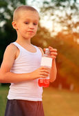Boy Child caucasian drinking Juice Beverage plastic bottle hot weather summer day outdoor — Foto Stock