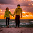 Couple Man and Woman in Love walking on Beach seaside holding hand in hand with Beautiful Sunset sky scenery People Romantic relationship and Friendship concept — Stock Photo