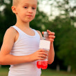 Boy Child caucasian drinking Juice Beverage plastic bottle hot weather summer day outdoor — Stock Photo