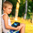 Boy Child playing with Tablet PC Outdoor with forest on backgrou — Foto de Stock