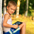 Stock Photo: Boy Child playing with Tablet PC Outdoor with forest on backgrou