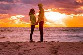 几个男人和女人在爱站在沙滩海边举行 h — 图库照片