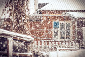 Snowfall Winter Weather in village with snowflakes and old house — ストック写真