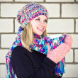 Young Woman with cofee cup Winter time wearing knitted sweater, hat and scarf with mittens Lifestyle concept trendy colors with white brick wall on background — Stock Photo #37490245