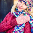 Stock Photo: Young Woman Beautiful happy smiling Face Winter time wearing knitted hat and scarf with mittens Lifestyle urban fashion style concept and Christmas holiday