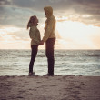 Couple Man and Woman in Love standing on Beach seaside holding hand in hand with Beautiful Sunset sky scenery People Romantic relationship and Friendship concept trendy moody colors — Stock Photo