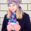 Stock Photo: Young beautiful Womdrinking hot coffee wearing winter knitted hat and mittens clothing Lifestyle concept with white brick wall on background