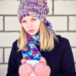 Young beautiful Woman drinking hot coffee wearing winter knitted hat and mittens clothing Lifestyle concept with white brick wall on background — Stock Photo #37667639