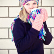 Young beautiful Woman drinking hot coffee wearing winter knitted hat and mittens clothing Lifestyle concept with white brick wall on background — Stock Photo #37667775
