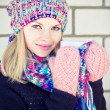 Young Woman happy smiling Face with coffee cup Winter time wearing knitted sweater, hat and scarf with mittens Lifestyle concept with white brick wall on background — Stock Photo