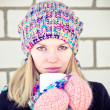 Young beautiful Woman drinking hot coffee wearing winter knitted hat and mittens clothing Lifestyle concept with white brick wall on background — Stock Photo #37667879