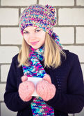 Young beautiful Woman drinking hot coffee wearing winter knitted hat and mittens clothing Lifestyle concept with white brick wall on background — Stock Photo