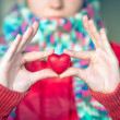 Heart shape love symbol in woman hands with face on background Valentines Day romantic greeting people relationship concept winter holiday — Stock Photo #38702375