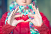 Heart shape love symbol in woman hands with face on background Valentines Day romantic greeting people relationship concept winter holiday — Zdjęcie stockowe
