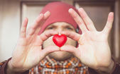 Heart shape love symbol in man hand with face on background Valentines Day romantic greeting people relationship concept winter holiday — Stock fotografie