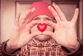 Heart shape love symbol in man hand with face on background Valentines Day romantic greeting people relationship concept winter holiday — Zdjęcie stockowe