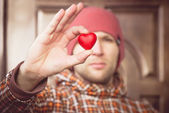 Heart shape love symbol in man hand with face on background Valentines Day romantic greeting people relationship concept winter holiday — Stockfoto