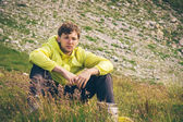 Man relaxing in mountains sitting on grass valley Traveling hiking summer recreation — Stock Photo