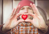 Heart shape love symbol in man hand with face on background Valentines Day romantic greeting people relationship concept winter holiday — Stock Photo