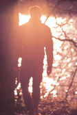 Moody blurred Background with defocused man silhouette back view going to river with lighting sun effects — Stock Photo