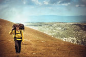 Man Traveler with Backpack hiking in Mountains Survival into the wild — Stock Photo