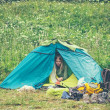 Tent Camping with woman traveler inside and tourism equipment backpack boots outdoor with beautiful green valley on background film effect colors — Stock Photo #40606955