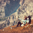 Stock Photo: WomTraveler with Backpack relaxing in Mountains with rocks on background mountaineering hiking sport lifestyle concept