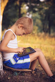 Boy Child playing with Tablet PC Outdoor with Summer nature on background Computer Game Dependence concept Lifestyle — Stock Photo